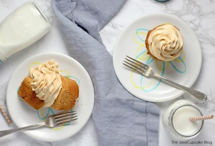 Peanut Butter Frosting on cupcakes served on white plates with a fork and a glass of milk