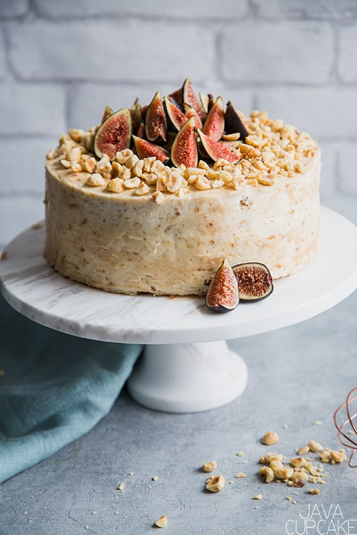 hazelnut and fig cake on a cake stand with a white background