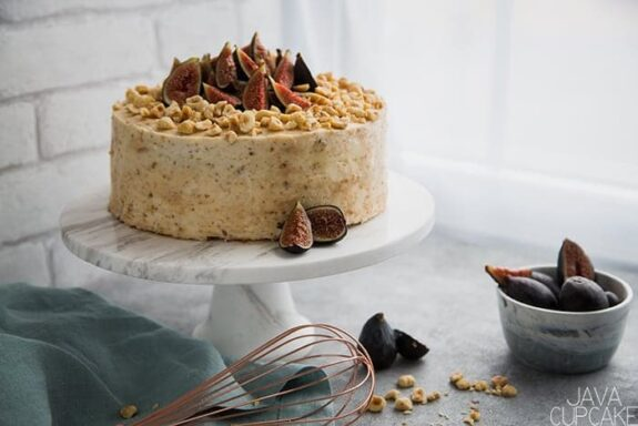 cake topped with figs and hazelnuts on a white background with a bowl of figs
