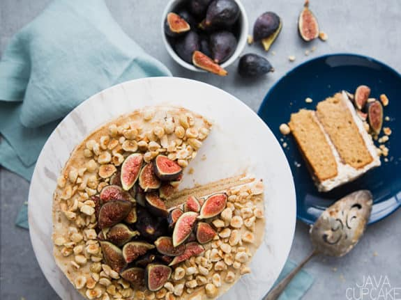 fig and hazelnut cake on a stand with a slice of cake on a plate and a bowl of figs