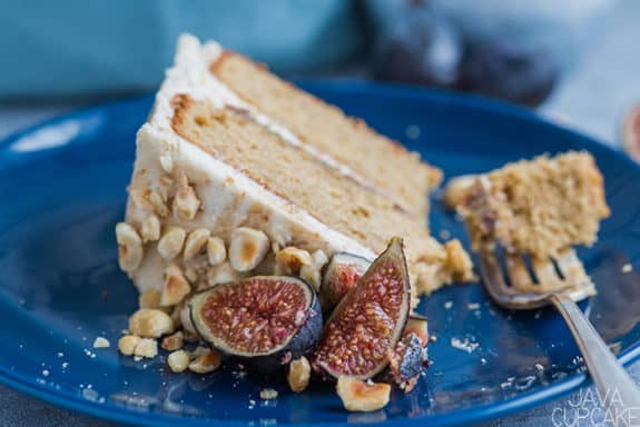 slice of hazelnut and fig cake on a blue plate with fresh sliced fig and chopped hazelnuts