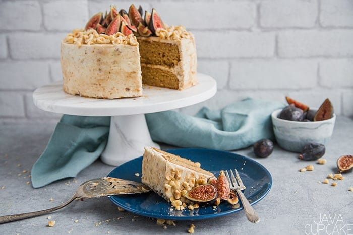 slice of hazelnut and fig cake on a blue plate with a hazelnut and fig cake on a cake stand