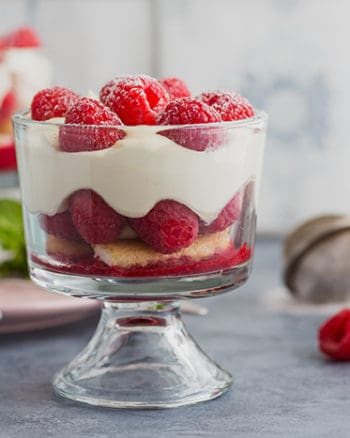 glass bowl of raspberries, biscuits, and cream on a counter