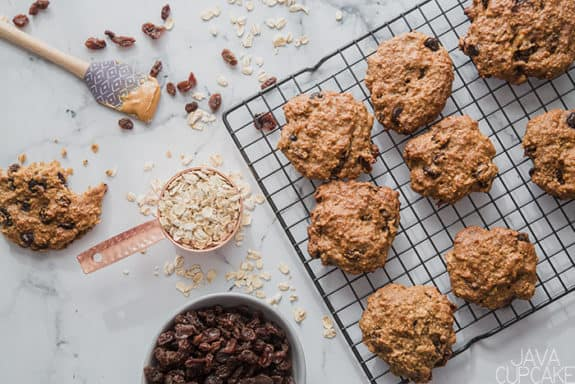 peanut butter oatmeal raisin cookies on a rack with a bowl of raisins and a bowl of oats