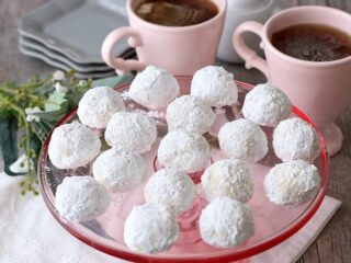 Russian tea cake balls served on top of a pink cake stand for visiting guests.