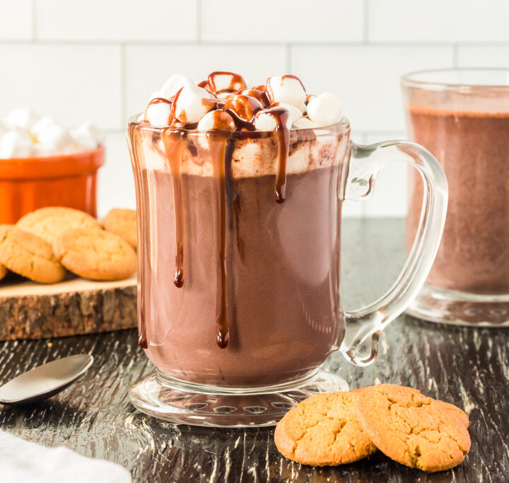 a glass mug full of hot chocolate topped with marshmallows and fudge